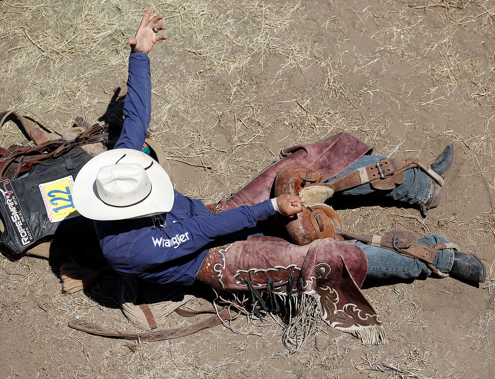 . Isaac Diaz of Desdemona, TX crunches down rosin on his saddle while preparing for to compete in saddle bronc riding during the finals of the California Rodeo Salinas at the rodeo grounds in Salinas on Sunday July 23, 2017. (David Royal/Herald Correspondent)