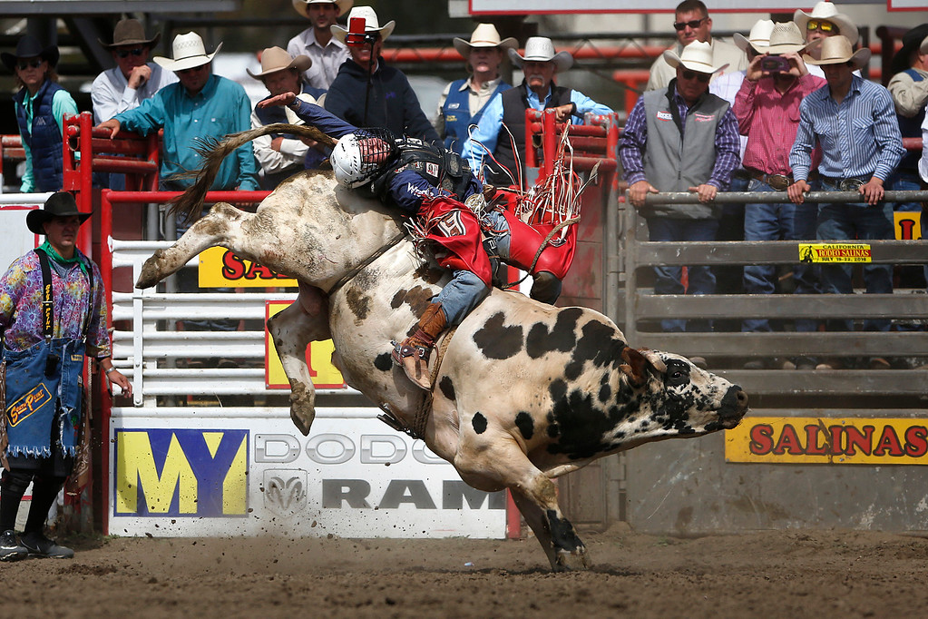 . Trey Benton III of Rock Island, TX hangs on to win the bull riding event during the finals of the California Rodeo Salinas at the rodeo grounds in Salinas on Sunday July 23, 2017. (David Royal/Herald Correspondent)