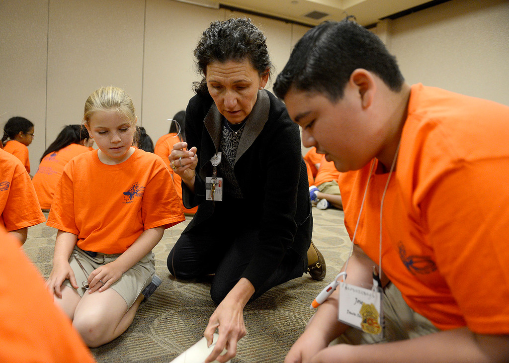 . Dr. Nadine Semer, MD works with Jenna Wynn, 10, and Jose Ramos, 12, who are participating in Salinas Valley Memorial Healthcare System�s (SVMHS) Medical Adventure Camp on Tuesday, July 25, 2017.  The students received hands on lesson on suturing. The class was taught by Dr. Semer who is a plastic surgeon currently a member of the Palliative Care team at SVMHS. The campers will learn about different types of sutures, techniques and will be able to perform sutures using foam and needleless sutures.  (Vern Fisher - Monterey Herald)