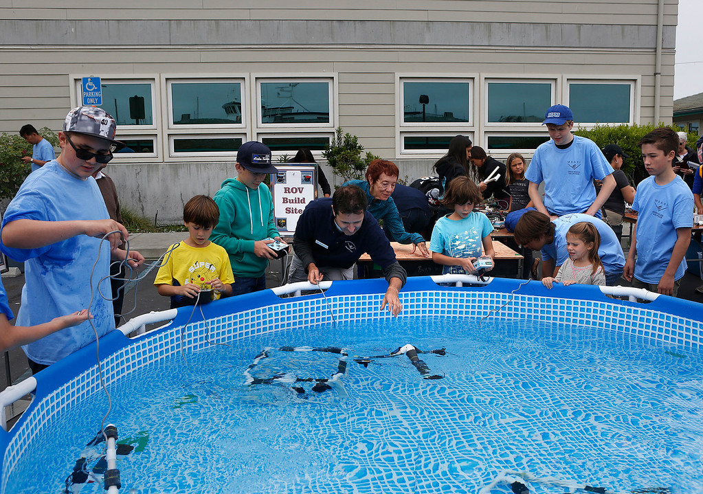. Monterey Bay Aquarium Research Institute principal engineer Mathieu Kemp. center, helps youngsters at a tank in the build your own remotely operated vehicle (ROV) area during the open house at MBARI in Moss Landing, Calif. on Saturday July 29, 2017. (David Royal/Herald Correspondent)
