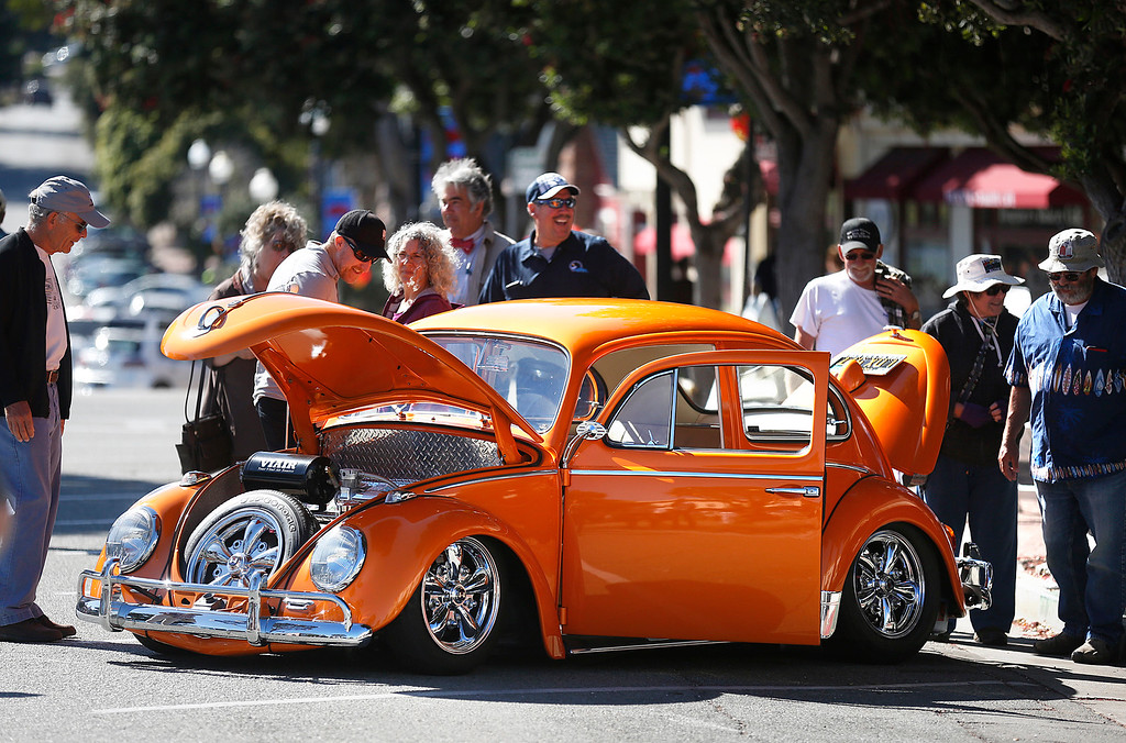 . Kris Machado, laughing at center, of Salinas attracts attention with his customized 1962 Volkswagen Bug during the Treffen 19 VW Cruise Show & Shine in Downtown Pacific Grove, Calif. on Wednesday July 26, 2017. The 19th Annual cruise from Canada to Mexico stopped in the city attracting local VW affectiandos owners and picked up drivers along the way. (David Royal/Herald Correspondent)