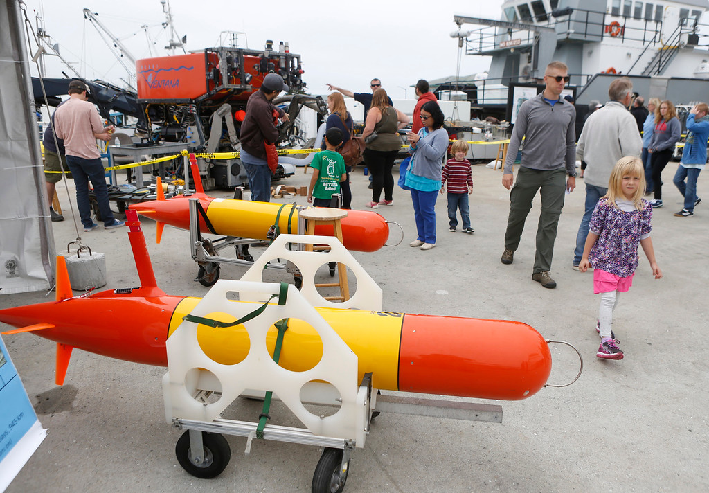 . Visitors walks past Tethys long range autonomous surface vehicles during the open house at MBARI in Moss Landing, Calif. on Saturday July 29, 2017. These particular ASVs are launched from a boat to survey chemical and biological structures to a depth of 300 meters in the ocean.  (David Royal/Herald Correspondent)