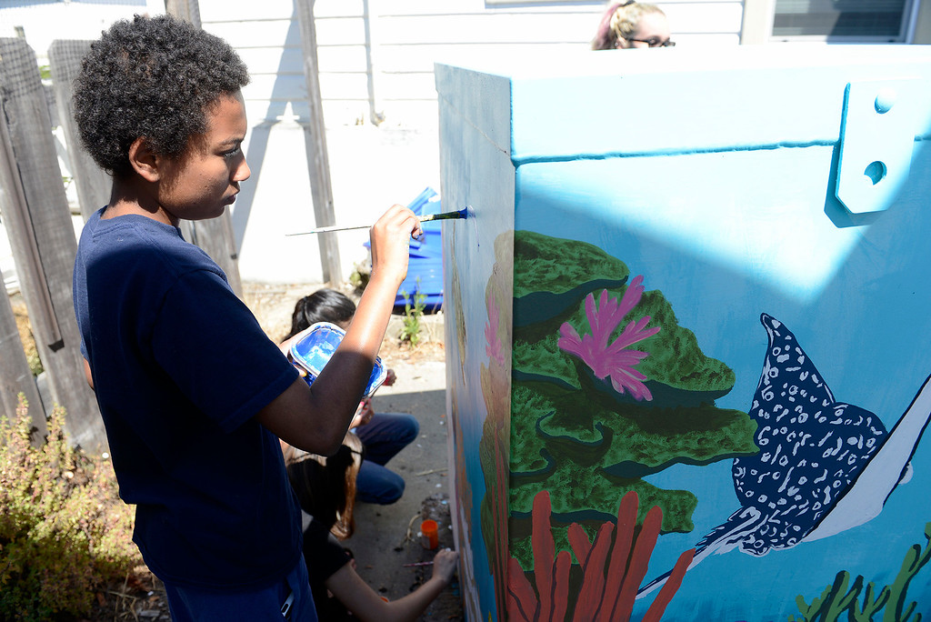 . Elijah Diallo, 15, with the Creative Painters Group with their finished utility boxes they painted in Monterey on Aug. 1, 2017.  (Vern Fisher - Monterey Herald)