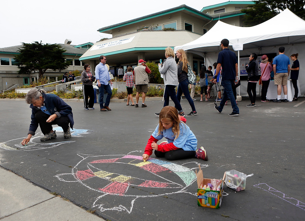 . Monterey Bay Aquarium volunteer Jean Smith and Monterey Bay Aquarium Research Institute volunteer Molly Conlin, 7, draw ocean creatures in chalk on the ground during the open house at MBARI in Moss Landing, Calif. on Saturday July 29, 2017. (David Royal/Herald Correspondent)