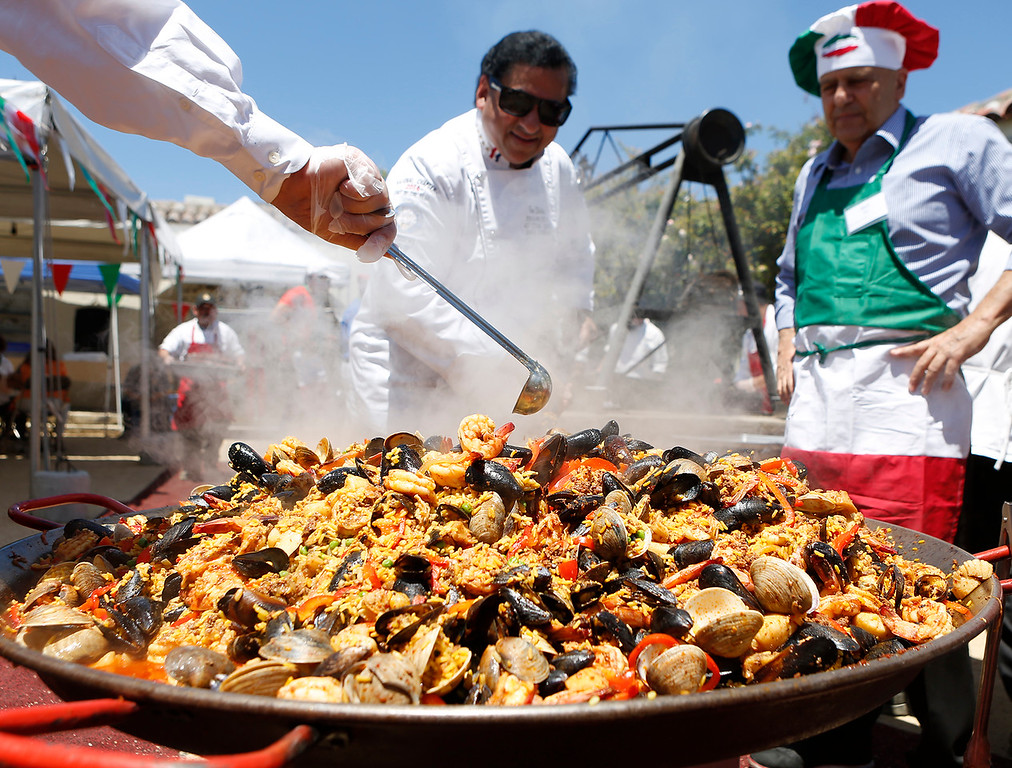 . Chef Tene Shake, center,  stirs a large pan filled with Spanish Paella as chef and restaurant owner Rich Pepe watches during La Merienda Celebration inside the Memory Garden at Custom House Plaza in Monterey on Saturday June 2, 2018. (David Royal/ Herald Correspondent)