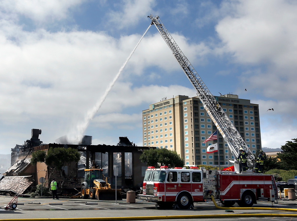 . Firefighters water down the Macdonald\'s on Canyon Del Rey in Seaside on Tuesday June 5, 2018. (David Royal/ Herald Correspondent)