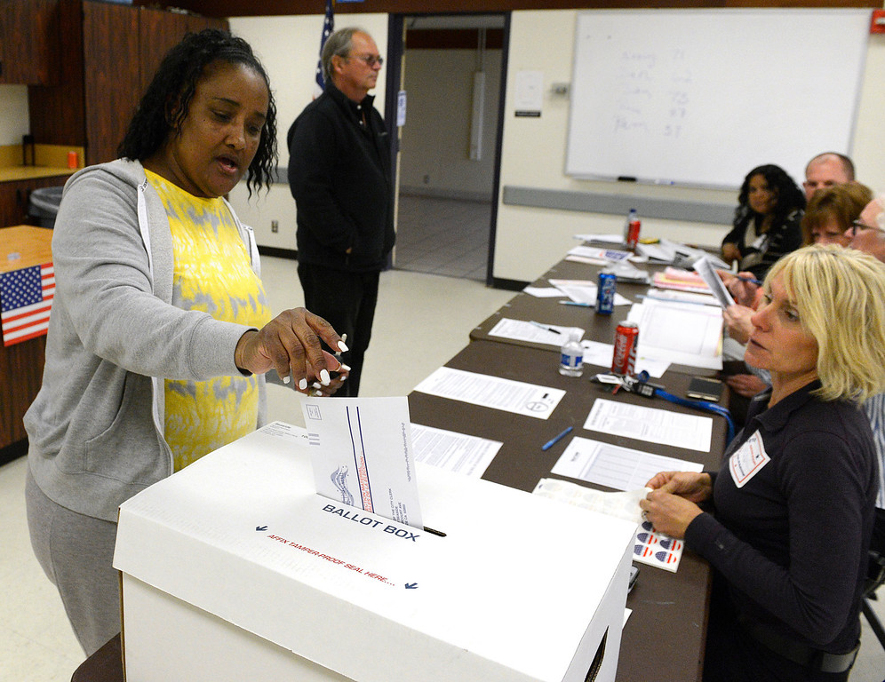 . Amanda Graham, left, drops her ballot into a collection box as Seaside Police commander Julie Veloz looks on at the Oldemeyer Center polling site in Seaside on Tuesday June 6, 2017. Special election ballots were cast on Tuesday for Measure L, an 1/2 cent sales tax increase to cover emergency and other general services and Measure G which would place a 10% tax on marijuana businesses.  (David Royal - Monterey Herald)