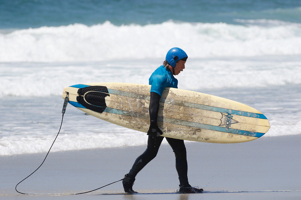 . Jim Waymann carries his surfboard after competing in the Kapuna Finals during the 37th annual Sunshine Freestyle Surfabout at Carmel Beach on Sunday, June 4, 2017 in Carmel By The Sea, Calif. (Vernon McKnight/Herald Correspondent)