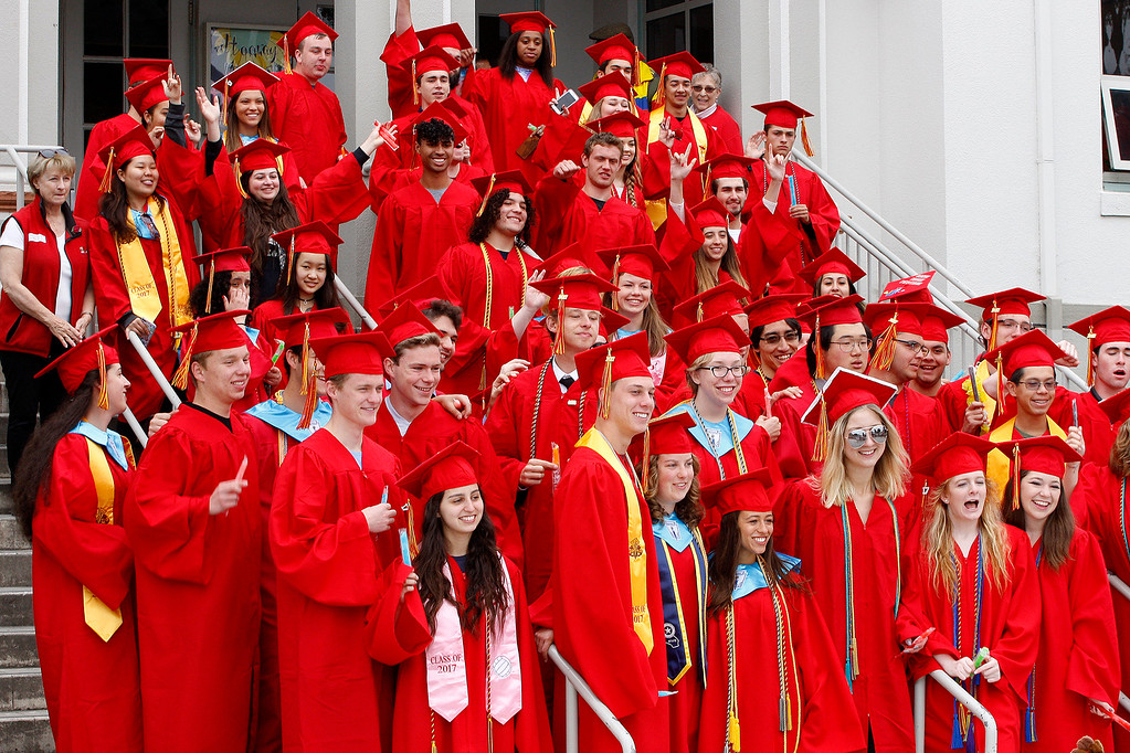 ". Graduating seniors from Pacific Grove High School pose for a group photo at Robert Down Elementary School on Friday, June 2, 2017.  The graduates walked the halls of Robert Down school ""high fiving\"" students and former teachers as a way to celebrate their graduation.  (Vern Fisher - Monterey Herald)"
