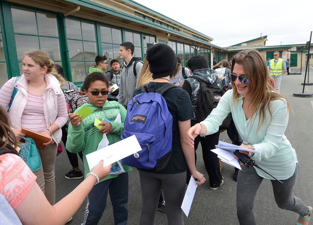 . Humanities teacher Bresiln Gaughn hands out report cards on the final day of the year at Bay View Academy\'s Upper School in Monterey on Thursday June 8, 2017. (David Royal - Monterey Herald)