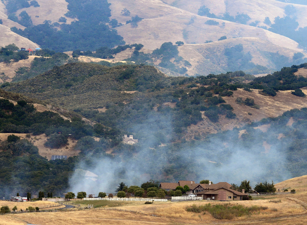 . Fire crews extinguish hotspots after a fire broke out off Castle Rock Road in rural Salinas on Wednesday June 7, 2017. Firefighters were able to contain the blaze to 15 acres. (David Royal - Monterey Herald)