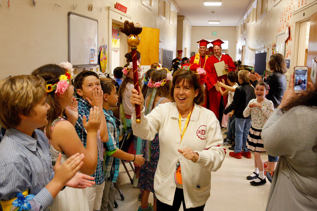 ". Robert Down Elementary School principal Linda Williams leads graduating seniors from Pacific Grove High School through the halls at Robert Down Elementary School on Friday, June 2, 2017.  The graduates walked the halls of Robert Down school ""high fiving\"" students and former teachers as a way to celebrate their graduation.  (Vern Fisher - Monterey Herald)"