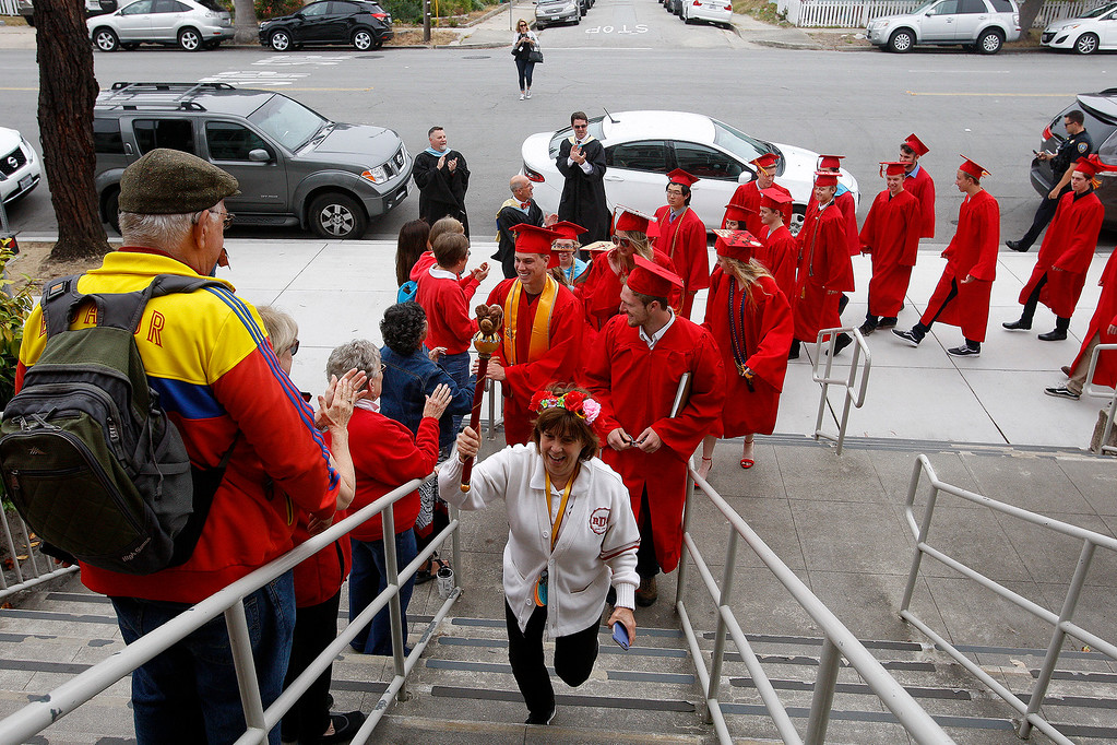 ". Robert Down Elementary School principal Linda Williams leads graduating seniors from Pacific Grove High School as they arrive at Robert Down Elementary School on Friday, June 2, 2017.  The graduates walked the halls of Robert Down school ""high fiving\"" students and former teachers as a way to celebrate their graduation.  (Vern Fisher - Monterey Herald)"