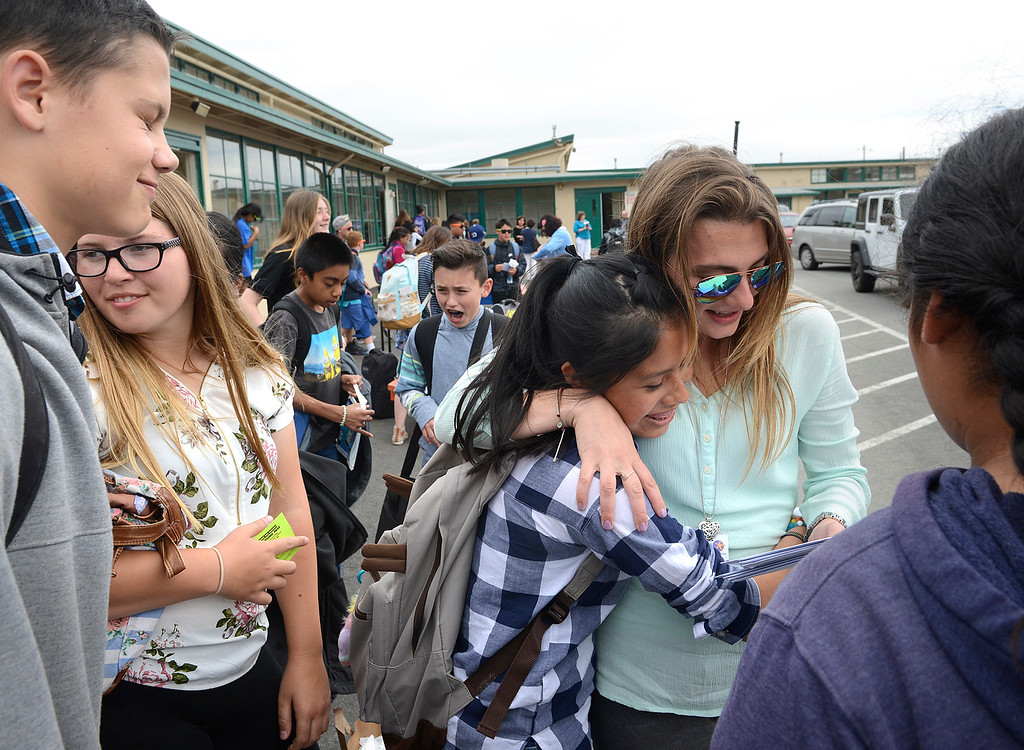 . Elsie Jeronimo, center, hugs humanities teacher Bresiln Gaughn as she hands out report cards on the final day of the year at Bay View Academy\'s Upper School in Monterey on Thursday June 8, 2017. (David Royal - Monterey Herald)