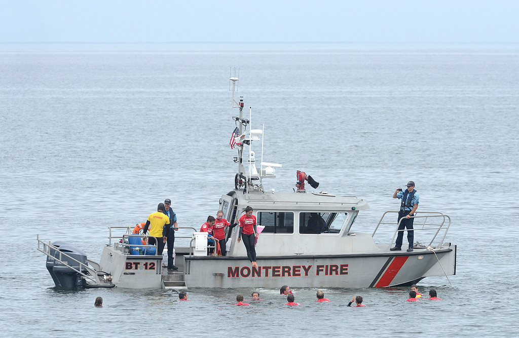 . California State junior lifeguard assistant Amanda Cavazos jumps off the Monterey fire boat with other assistants after swimming out for a tour of the vessel off Monterey State Beach on Wednesday June 7, 2017. A mock rescue was performed, Firefighters ran through an EMS call and gave a talk about the firefighting career during a demonstration day for the junior lifeguards. (David Royal - Monterey Herald)