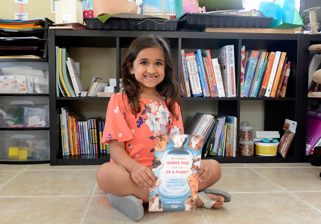 ". Inaya Khan, 6, holds a printout of the cover of Bedtime Math\'s new book ""How Many Guinea Pigs Can Fit on a Plane\"" at her home in Seaside on Wednesday June 7, 2017. Khan was one of just 50 kids around the world who\'s question was chosen for the book. (David Royal - Monterey Herald)"