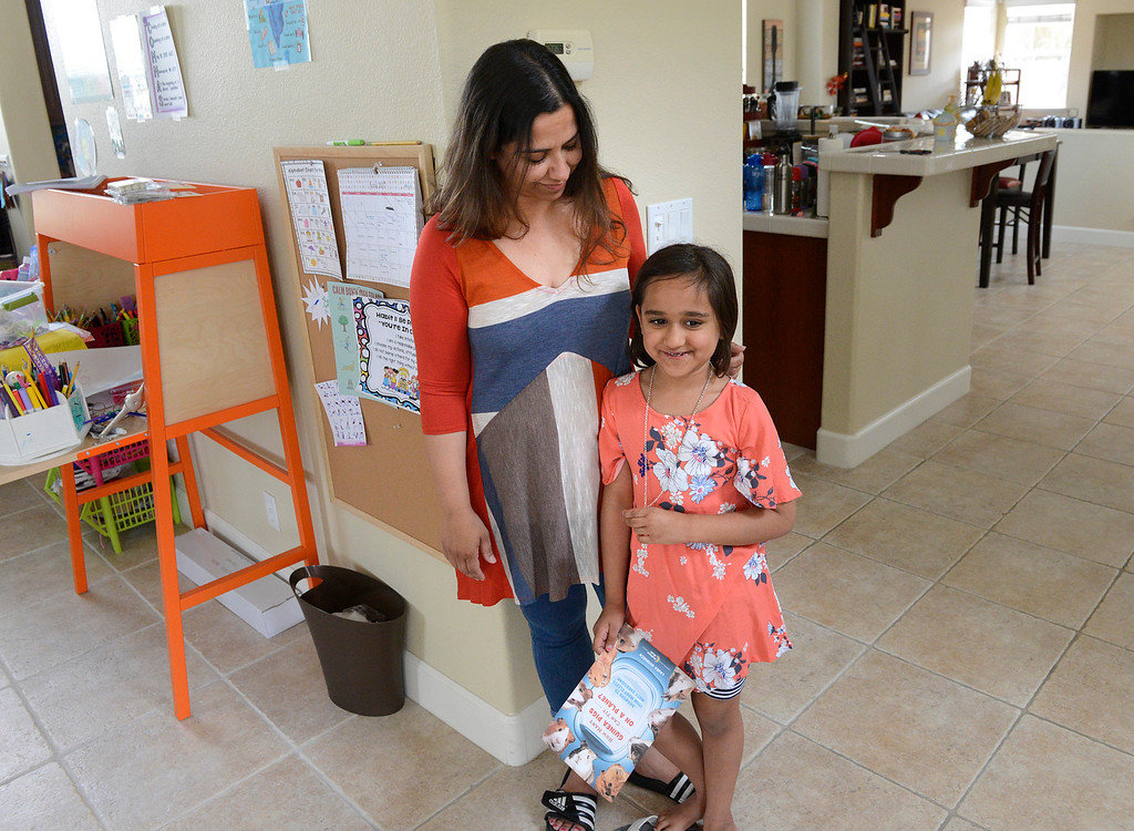 ". Inaya Khan, 6, leans against her mother Sadia while holding a printout of the cover of Bedtime Math\'s new book ""How Many Guinea Pigs Can Fit on a Plane\"" at her home in Seaside on Wednesday June 7, 2017. Khan was one of just 50 kids around the world who\'s question was chosen for the book. (David Royal - Monterey Herald)"