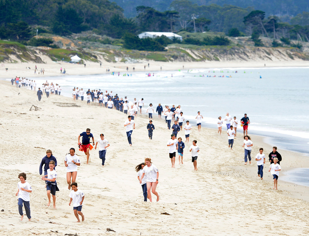 . California State junior lifeguards complete a training run on Monterey State Beach in Monterey on Wednesday June 7, 2017. (David Royal - Monterey Herald)