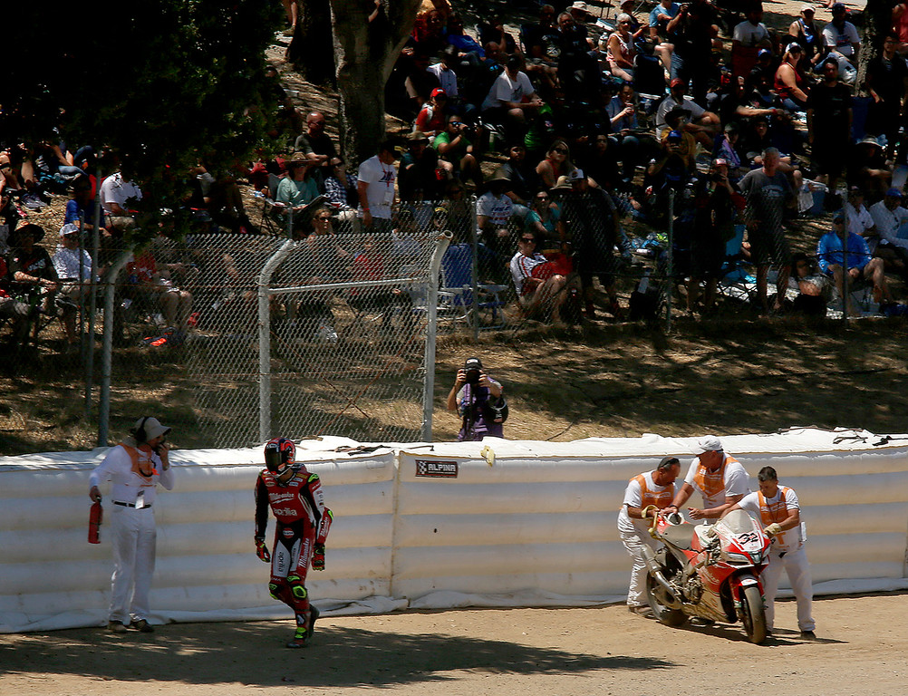 . Milwaukee Aprilla racer Lorenzo Salvadori walks off after crashing in tThe Corkscrew during Race 2 of the Superbike World Championship at Laguna Seca Raceway in Monterey on Sunday June 24, 2018. Kawasaki Racing Teams Jonathan Rea of Great Britain won the race. (David Royal/ Herald Correspondent)