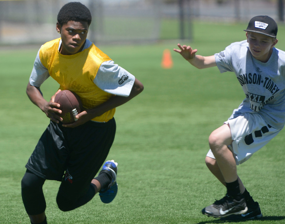. Jayden Russell runs the ball while scrimmaging in his 12-14 year-old group during the Johnson-Toney Football Camp at Monterey Peninsula College on Monday June 26, 2017. (David Royal - Monterey Herald)