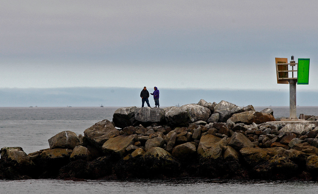 . Two people stand on the north jetty at Moss Landing Harbor during a foggy morning on Tuesday, June 27, 2017.  (Vern Fisher - Monterey Herald)