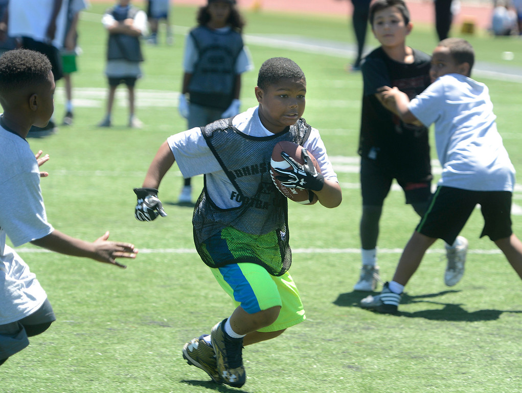 . Rashad Darensburg, 9 runs the ball while scrimmaging in his 9-11 year-old group during the Johnson-Toney Football Camp at Monterey Peninsula College on Monday June 26, 2017. (David Royal - Monterey Herald)