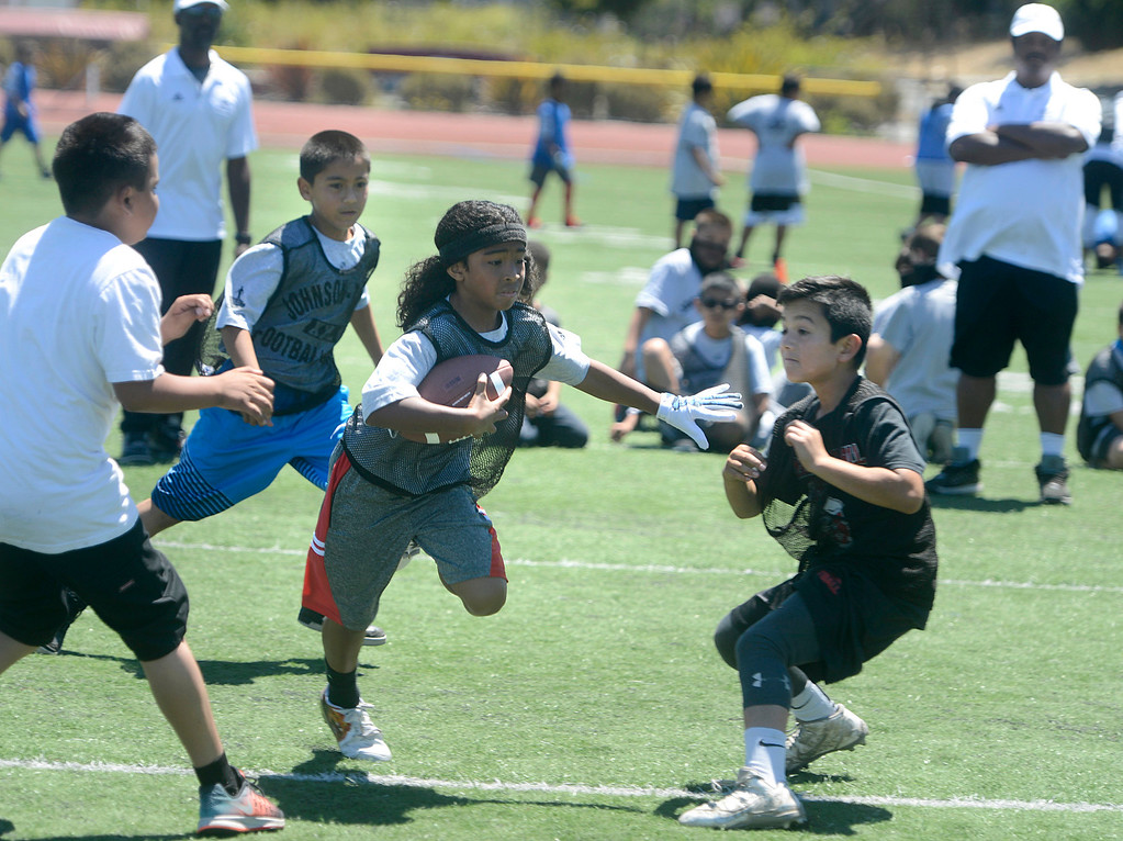 . Ryland Gaskins, 9 runs the while scrimmaging in his 9-11 year-old group during the Johnson-Toney Football Camp at Monterey Peninsula College on Monday June 26, 2017. (David Royal - Monterey Herald)