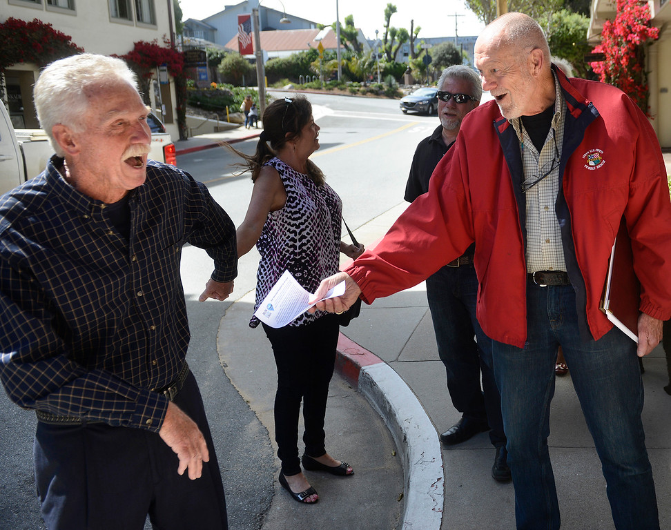 . Local hospitality businessman Sam Teel, left, avoids a flyer held out by Public Water Now managing director George Riley before entering a presentation to local business leaders by CalAm attorney Joe Conner at the Monterey Plaza Hotel and Spa on Tuesday June 27, 2017. Members of Public Water Now were eventually allowed to attend the event when the promised to behave. (David Royal - Monterey Herald)