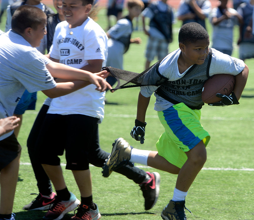 . Rashad Darensburg, 9 runs the ball while scrimmaging in his 12-14 year-old group during the Johnson-Toney Football Camp at Monterey Peninsula College on Monday June 26, 2017. (David Royal - Monterey Herald)