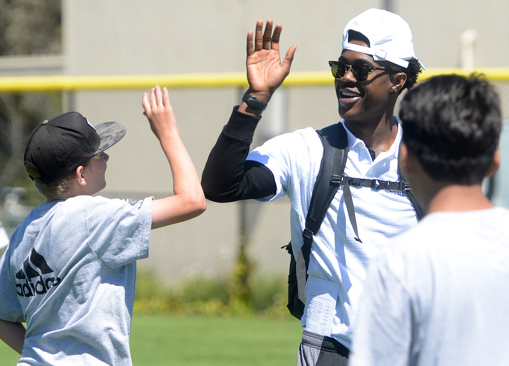 . Chris Evans greets one of his 12-14 year-olds after he made a big play while scrimmaging during the Johnson-Toney Football Camp at Monterey Peninsula College on Monday June 26, 2017. (David Royal - Monterey Herald)