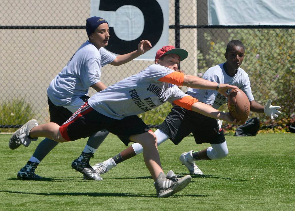 . Ra Seva\'aetasi makes an interception on a pass intended for Sean Irving, right, as teammate Elijah Stringer looks on while scrimmaging in his 12-14 year-old group during the Johnson-Toney Football Camp at Monterey Peninsula College on Monday June 26, 2017. (David Royal - Monterey Herald)