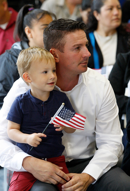 . Jimmy Vanhove from France with his son James, 3, prepares to take the oath of allegiance at the Independence Day Naturalization Ceremony at Hartnell College in Salinas on Tuesday, July 3, 2018.  (Vern Fisher - Monterey Herald)