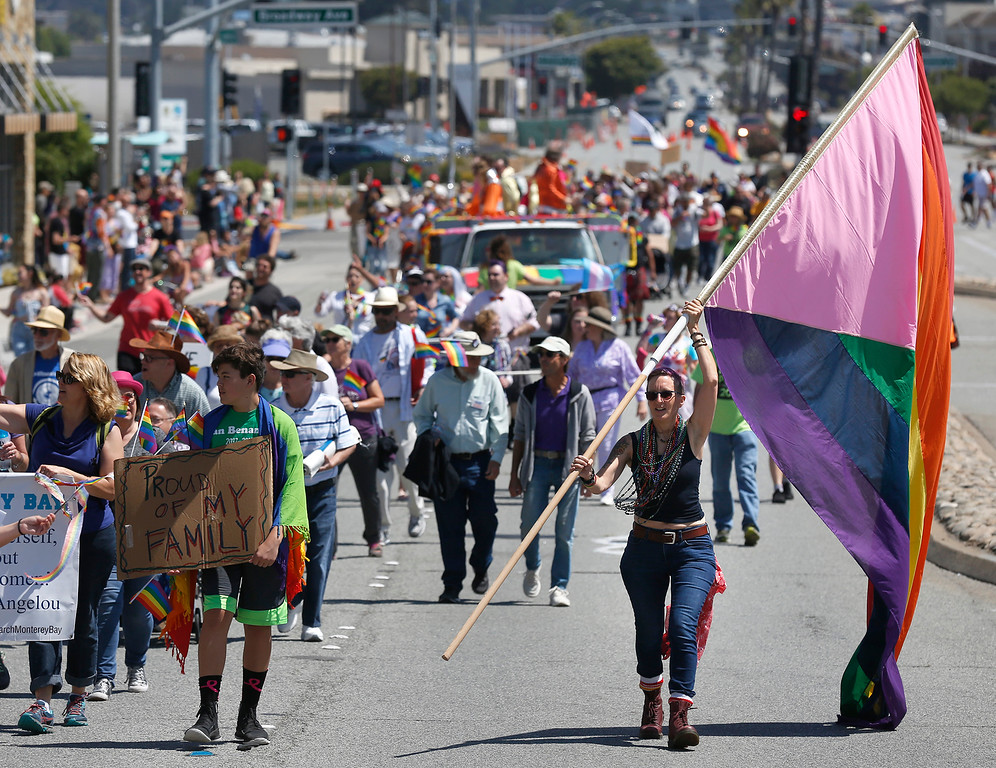 . Lesley Harrison carried a large rainbow flag while down Fremont Street during the Monterey Peninsula Pride Parade in Seaside on Saturday June 30, 2018. (David Royal/ Herald Correspondent)