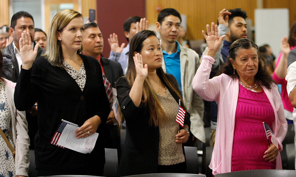 . New U.S. citizens take the oath of allegiance at the Independence Day Naturalization Ceremony at Hartnell College in Salinas on Tuesday, July 3, 2018.  (Vern Fisher - Monterey Herald)