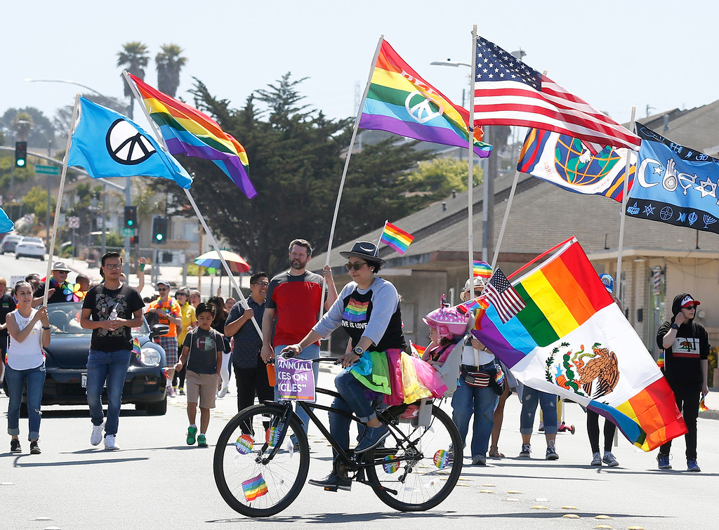 . Elizabeth Serrato rode her bicycle with her daughter Skylerblu, 2, during the Monterey Peninsula Pride Parade in Seaside on Saturday June 30, 2018. (David Royal/ Herald Correspondent)