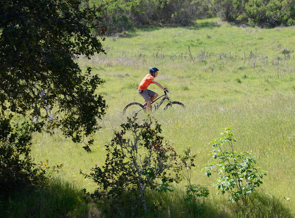 . A young mountain biker rides on lower Ollason Trail which is normally closed to bicycles but was closed to all due to erosion and downed trees at Toro Park in rural Salinas on Thursday March 16, 2017. (David Royal - Monterey Herald)