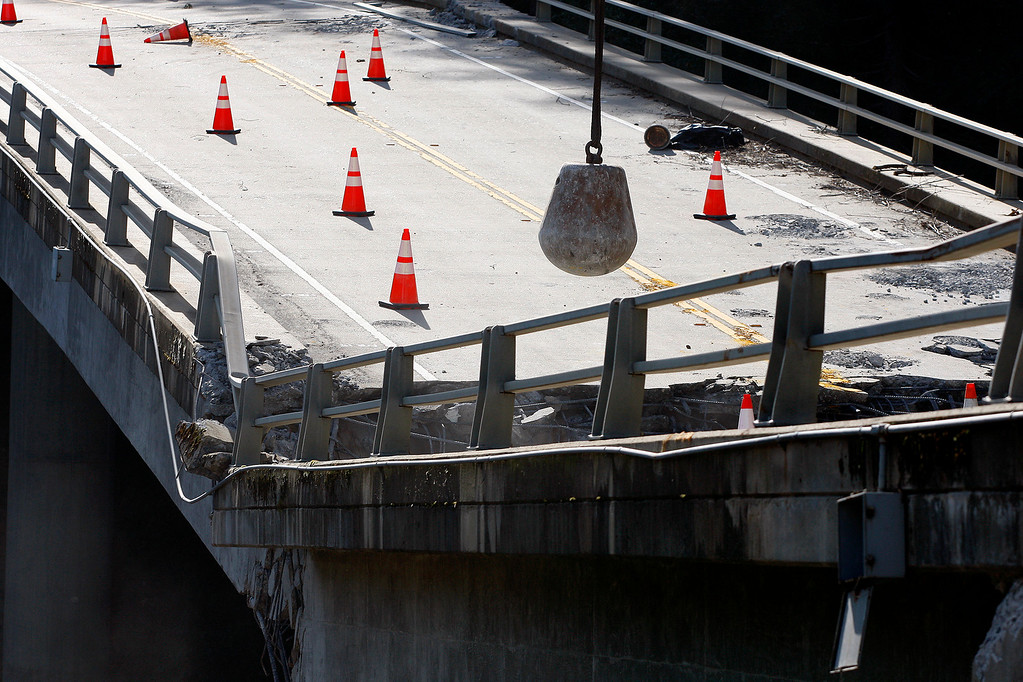 . Crews use a 6,000 pund wrecking ball attached to a crane on the demolition of the storm damaged Pfeiffer Canyon Bridge in Big Sur on Thursday, March 16, 2017.  (Vern Fisher - Monterey Herald)
