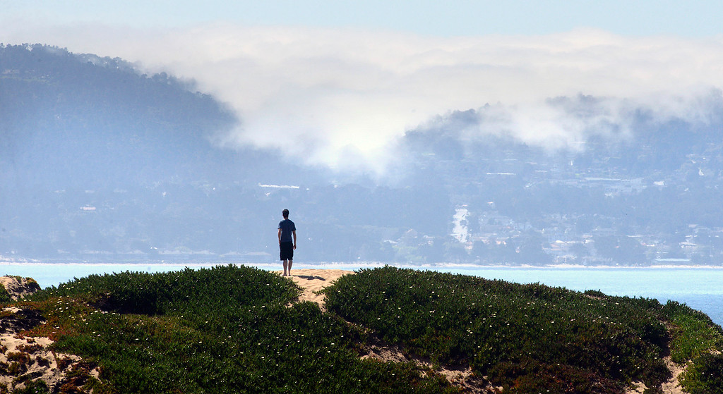 . A young man looks out over the bay from Fort Ord Dunes State Park as fog hangs on Carmel Hill as warm weather basks Monterey County on Tuesday March 14, 2017. (David Royal - Monterey Herald)