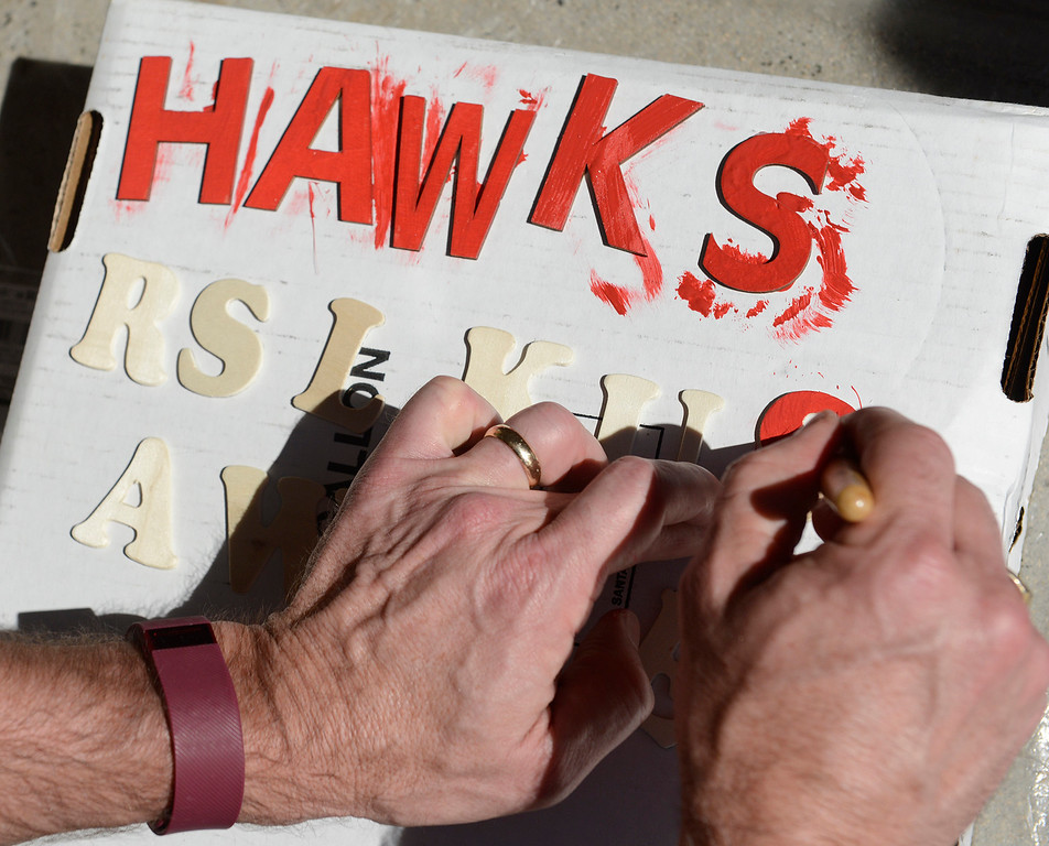 . A volunteer paints letters for hawk a hawk-themed playhouse for the Porter Youth Center during the launching of the Habitat for Humanity Playhouse Build Program at the Habitat for Humanity ReStore in Seaside on Tuesday March 14, 2017. Employees from Sponsor Brown-Forman built eight playhouses that will be donated to local schools and youth centers. (David Royal - Monterey Herald)
