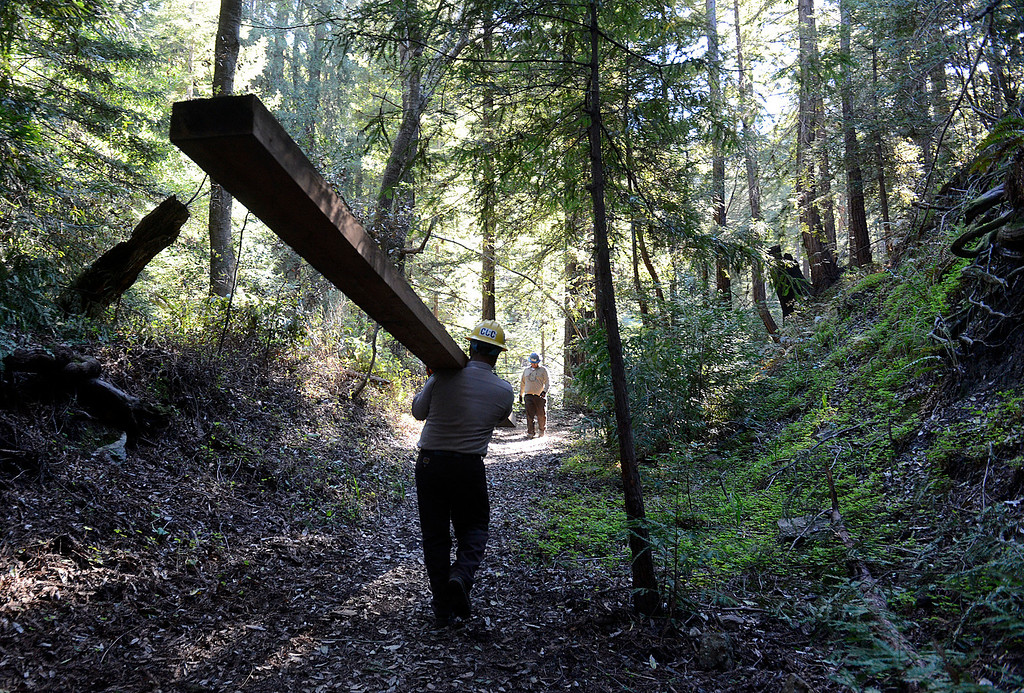 . A California Conservation Corps crew member carries a piece of lumber up while building the temporary Pfeiffer Canyon access trail so residents and employees can get around the damages Pfeiffer Canyon Bridge on Highway 1 in Big Sur, Calif. on Monday March 13, 2017. The bridge was compromised after slides occurred in the area associated with this winter\'s heavy rains.  (David Royal - Monterey Herald)