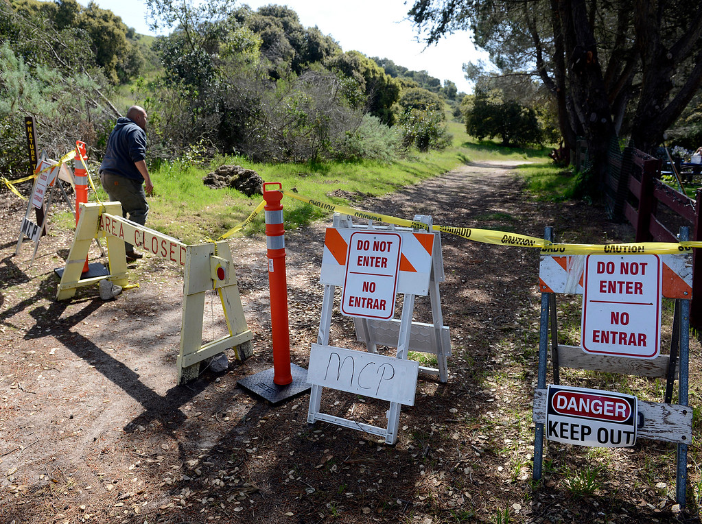 . Toro Park building and grounds supervisor Hector Campos walks past  signs fencing off Ollason Road while looking at trail conditions at the park in rural Salinas on Thursday March 16, 2017. Campos said that 97% of the trails are closed due to erosion, downed trees and other storm damage.  (David Royal - Monterey Herald)