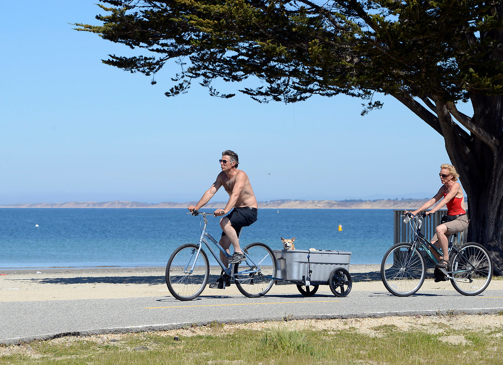 . Kyle and Sonya Sinorella ride bikes past Window on the Bay Park in Monterey with their dogs Lilyrose and Sonya as warm weather basks Monterey County on Tuesday March 14, 2017. (David Royal - Monterey Herald)