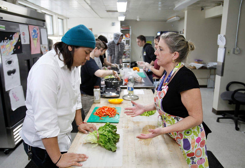 . Central Coast High School student Marco Rios gets instruction from chef Kari Bernardi in the culinary academy kitchen in Seaside with chef Kari Bernardi on Wednesday, March 15, 2017.  (Vern Fisher - Monterey Herald)