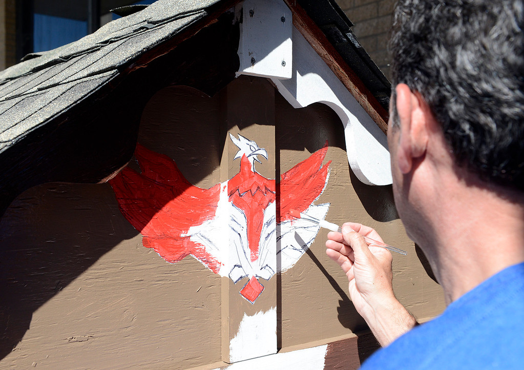 . Mike Keyes of Louisville, KY paints a hawk on the outside of a hawk-themed playhouse for the Porter Youth Center during the launching of the Habitat for Humanity Playhouse Build Program at the Habitat for Humanity ReStore in Seaside on Tuesday March 14, 2017. Employees from Sponsor Brown-Forman built eight playhouses that will be donated to local schools and youth centers. (David Royal - Monterey Herald)