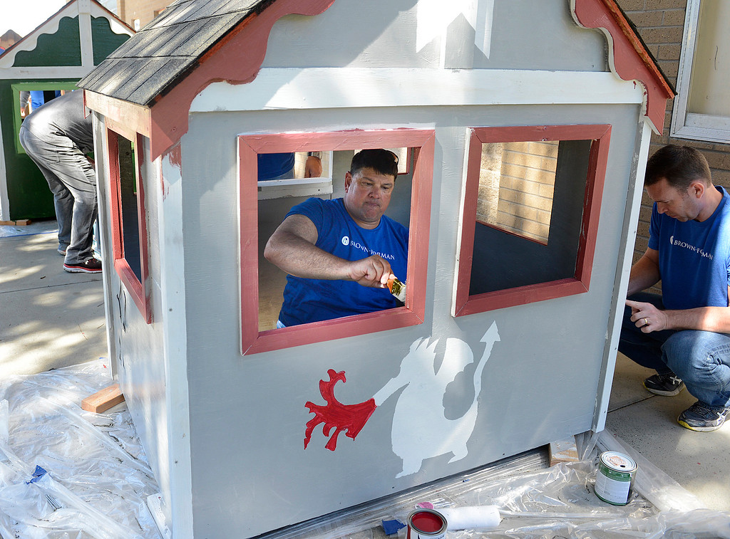 . Mark Schuetz paints the inside of a playhouse for the Army Community Services during the launching of the Habitat for Humanity Playhouse Build Program at the Habitat for Humanity ReStore in Seaside on Tuesday March 14, 2017. Employees from Sponsor Brown-Forman built eight playhouses that will be donated to local schools and youth centers. (David Royal - Monterey Herald)