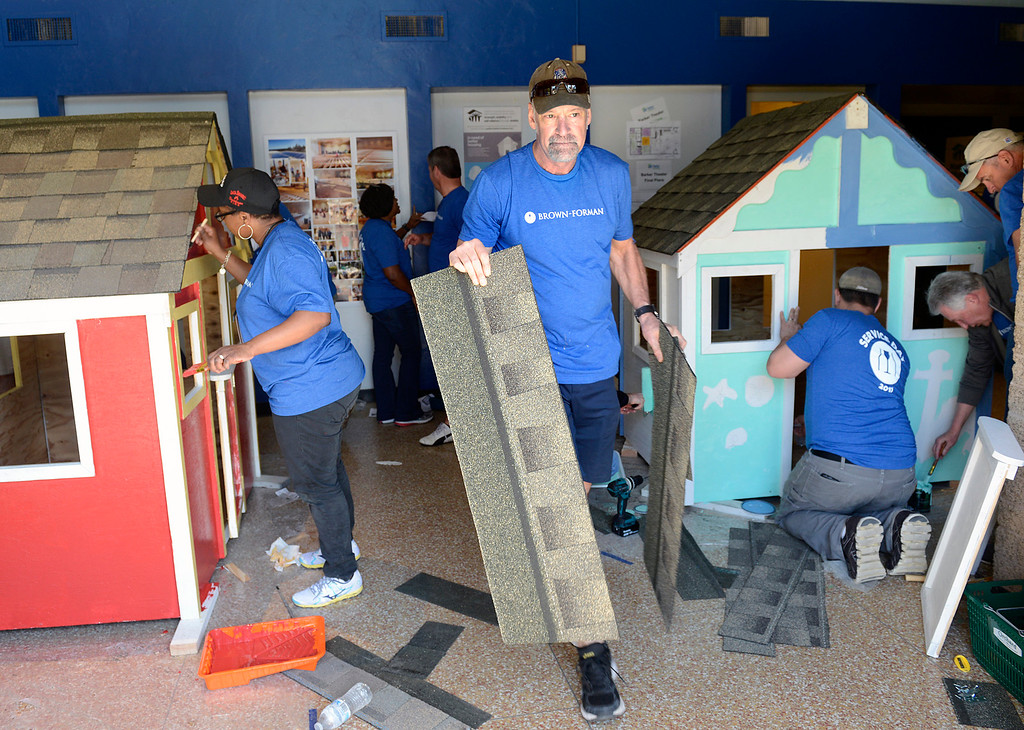. Paul Power of Bedford New Hampshire carries a roof shingle past Daniel Goodson, left, of New York City as she paints a playhouse for the Porter Youth Center, left, during the launching of the Habitat for Humanity Playhouse Build Program at the Habitat for Humanity ReStore in Seaside on Tuesday March 14, 2017. The playhouse at right is for the Seaside YMCA. Employees from Sponsor Brown-Forman built eight playhouses that will be donated to local schools and youth centers. (David Royal - Monterey Herald)