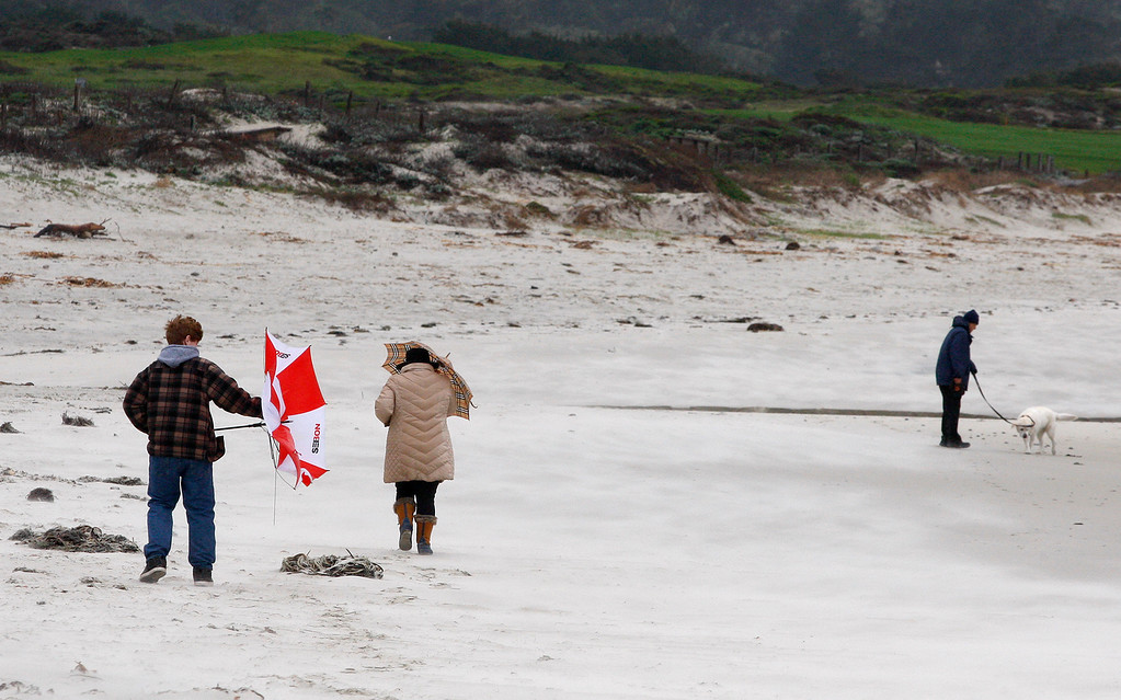 . Two people walking on Asilomar State Beach in Pacific Grove get hit by wind and rain on Thursday, March 22, 2018.  (Vern Fisher - Monterey Herald)