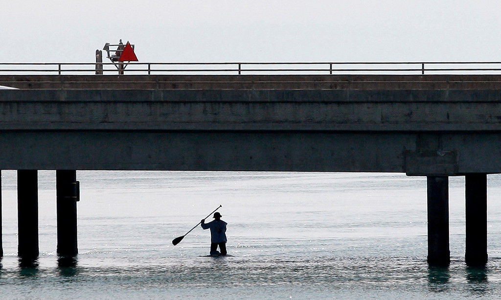 . A paddle boarder makes his way under Highway One in the Elkhorn Slough on Monday, March 19, 2018.  (Vern Fisher - Monterey Herald)