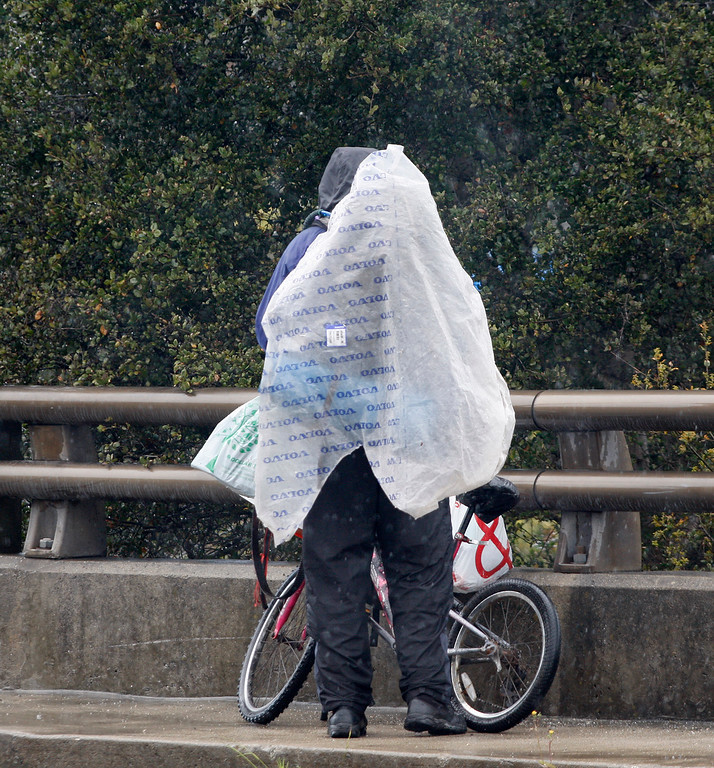 . A man uses a plastic bag to protect himself from the heavy rain in Monterey on Friday, March 16, 2018.  (Vern Fisher - Monterey Herald)