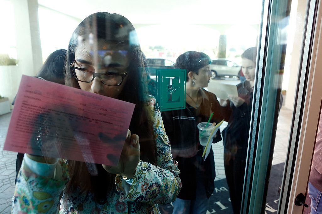 . Annalise Rodriguez, 21, of Watsonville  signs forms describing herself on a door while waiting in line with thousands of others during open casting for HBO\'s Big Little Lies at Embassy Suites in Seaside on Saturday March 17, 2018. (David Royal/ Herald Correspondent)